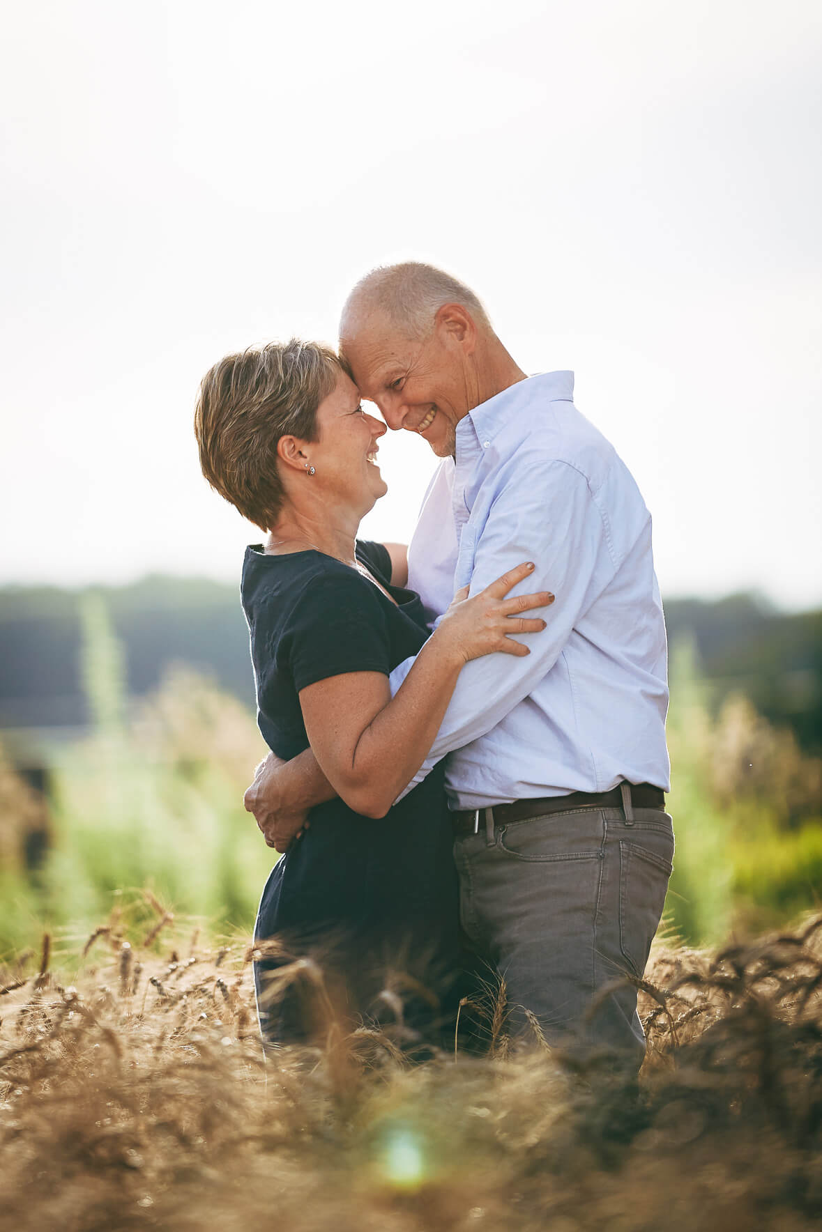 Portrait photo of a couple hugging and smiling in a wheat field in Kitchener
