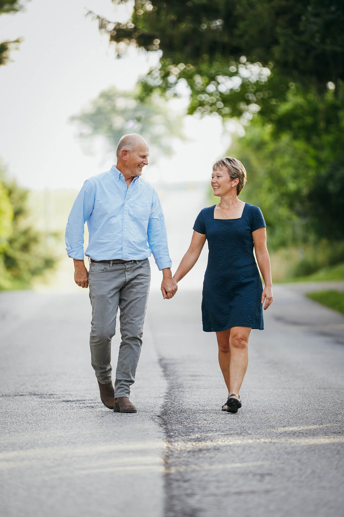 Husband and wife holding hands and laughing while walking on a road