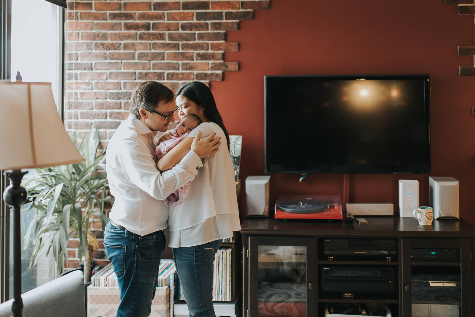 Mom and dad cuddling baby in their home during lifestyle shoot
