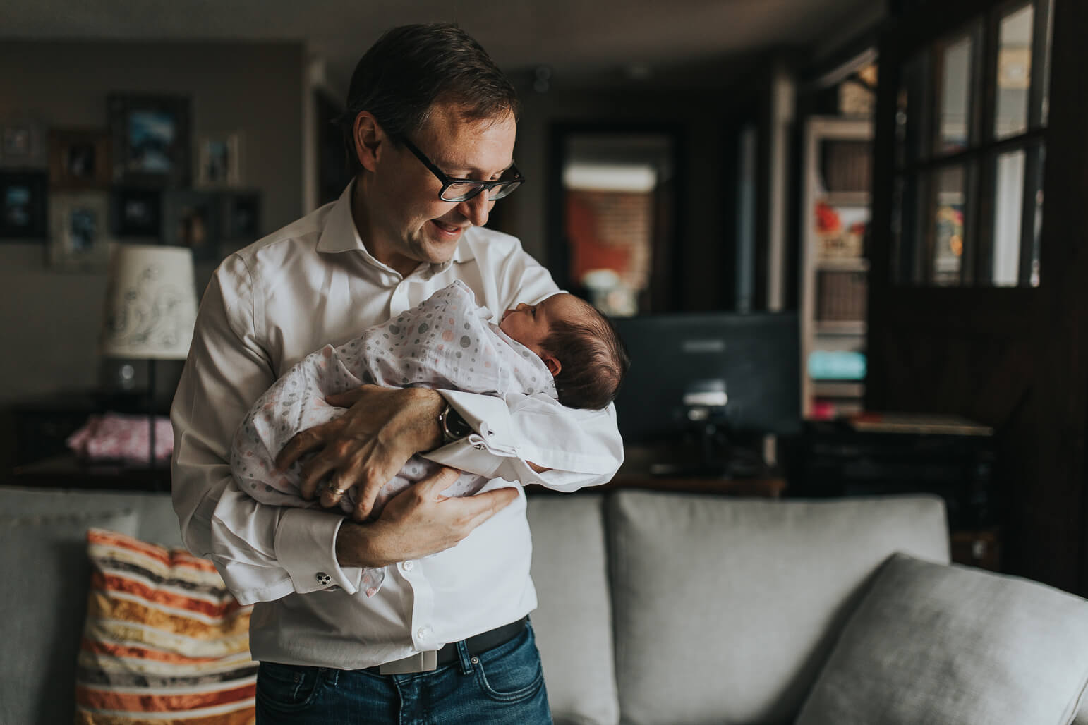 A father holding his baby girl in the living room during a Toronto lifestyle newborn shoot