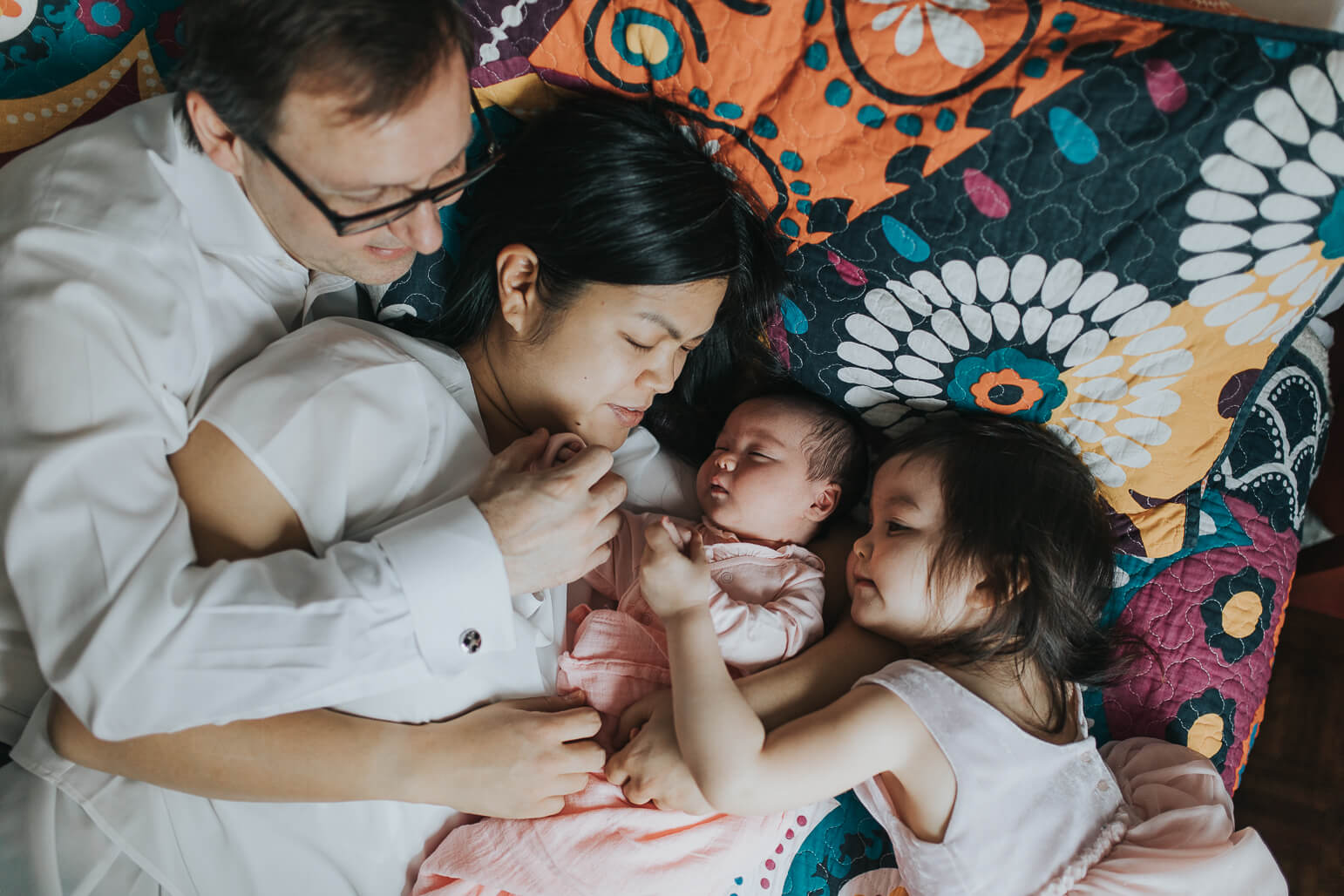 Entire family lying on bed with the newborn during a lifestyle shoot.