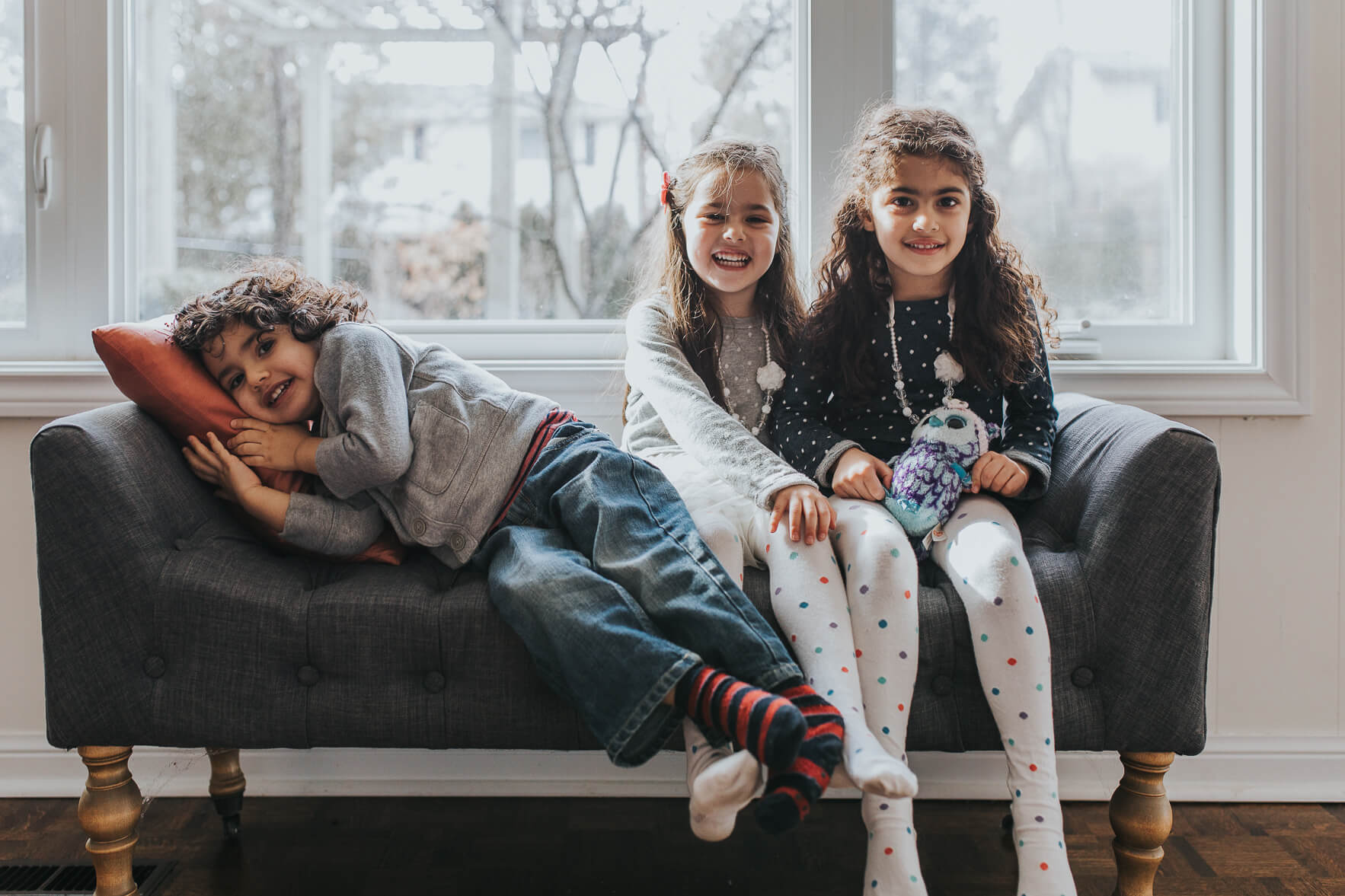Brother and his twin sisters laughing on a couch