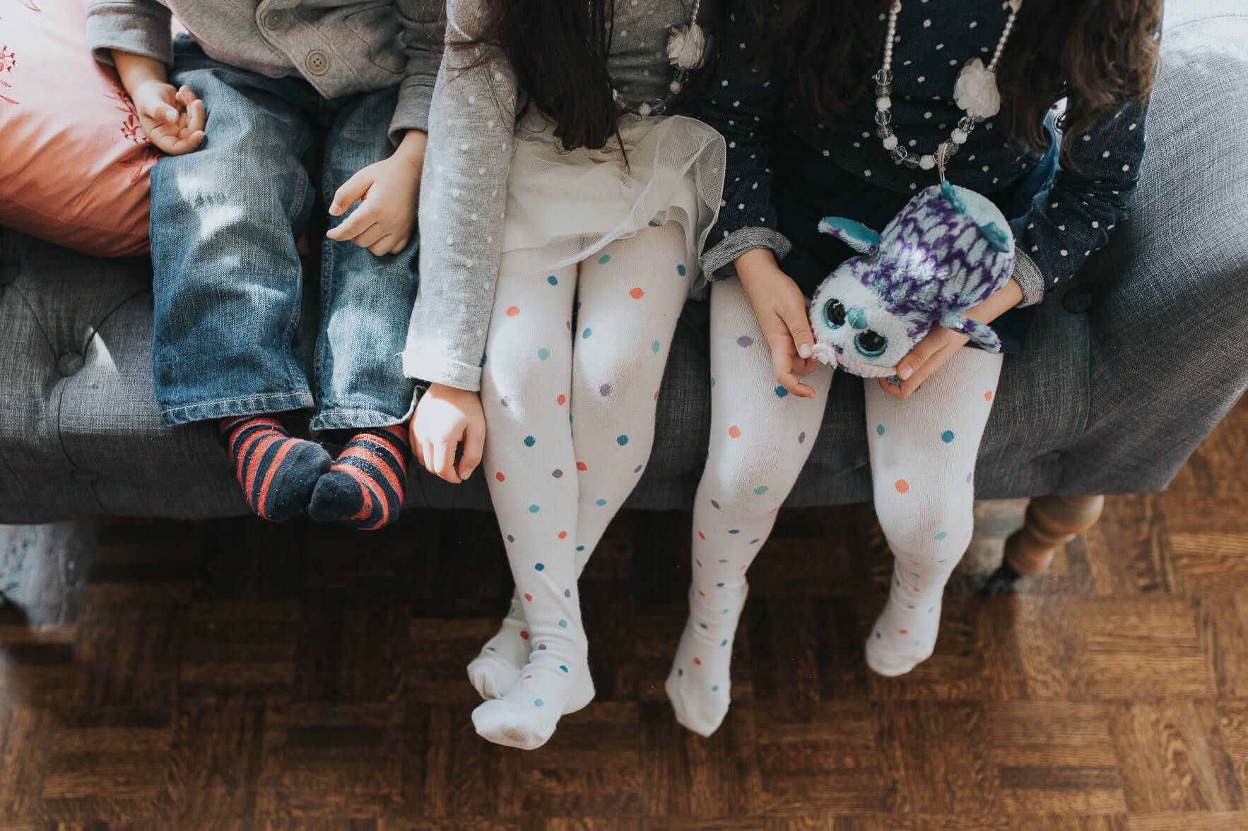 Top down shot of three kids with their socks on