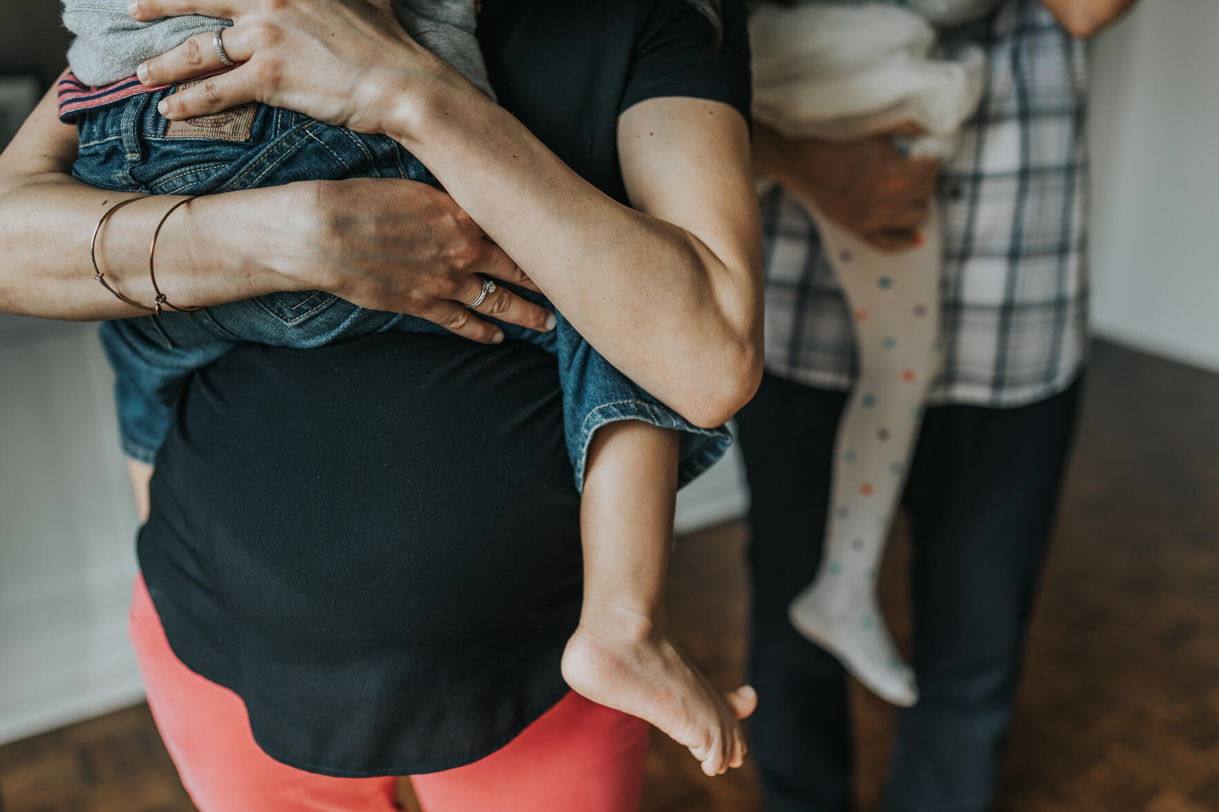 Close up detail shot of mom holding her son with her belly showing off