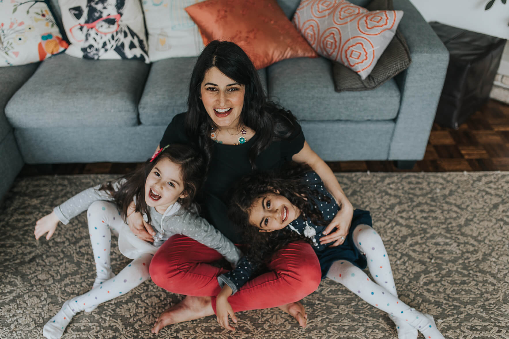 Mom in a yoga pose with her two daughters laughing