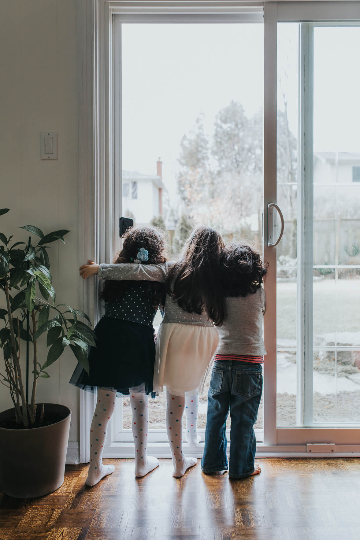 Three kids standing by the door looking into the backyard in a Port Credit home in Toronto