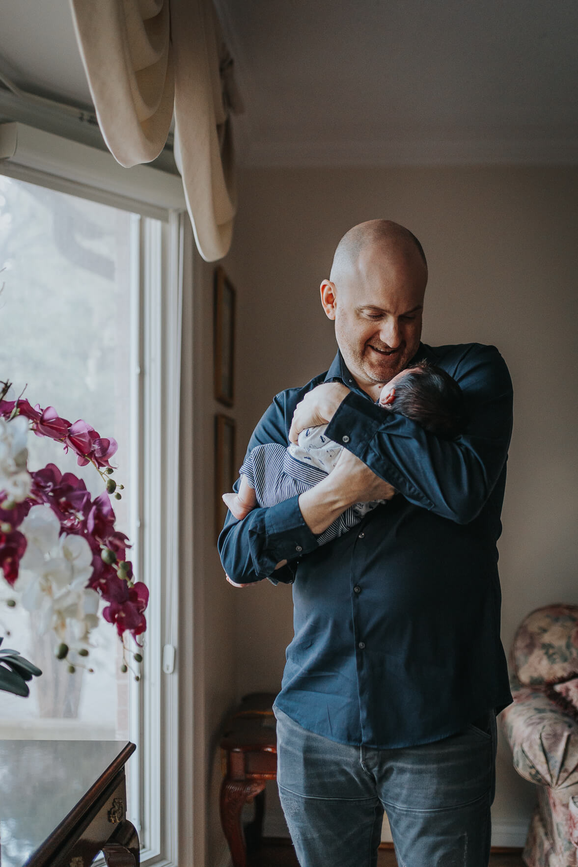 New dad holding his infant son near the window of a Toronto house.