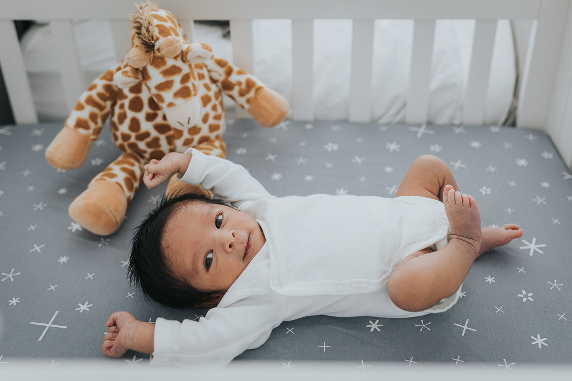 Newborn baby boy stretching in his crib in his parents' Toronto condo.
