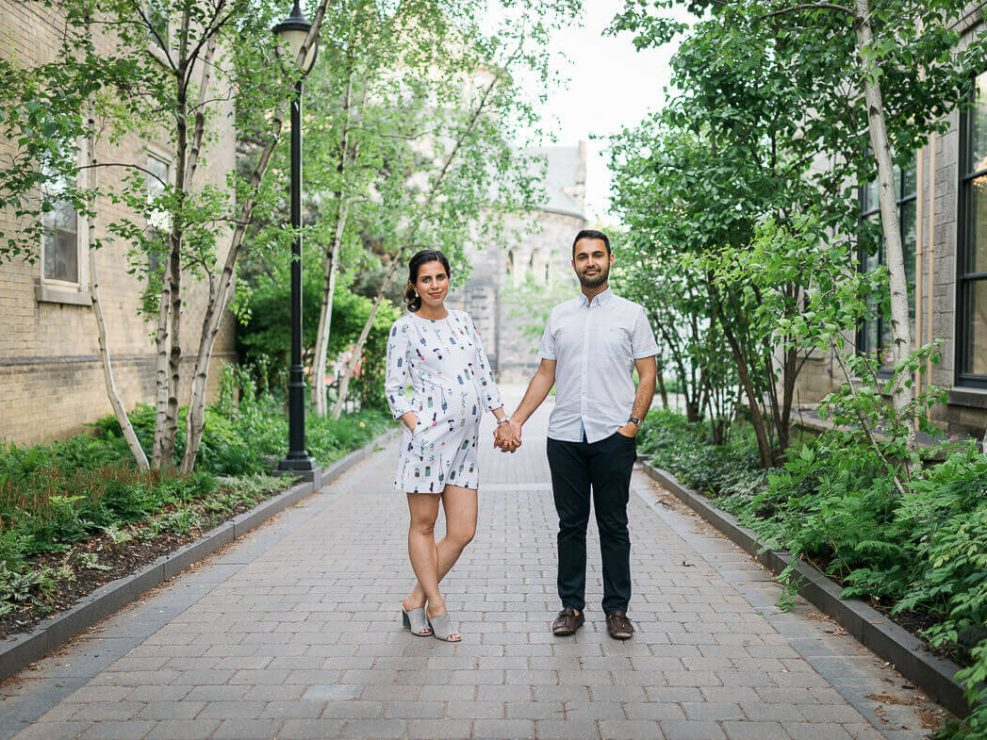 Pregnant woman in short dressing holding hands with husband at University of Toronto campus
