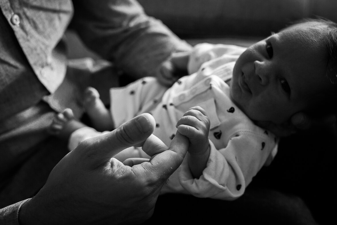 Black and white photo of baby's tiny hand holding his dad's finger.