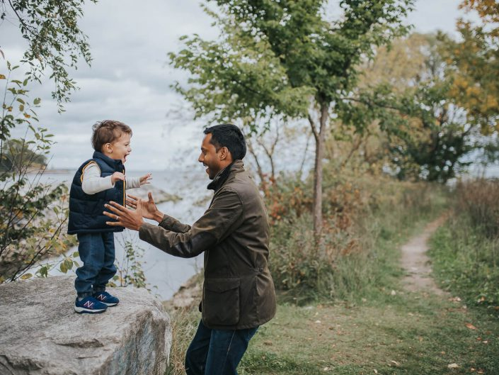 Son jumping into father's arms during fall family photo shoot
