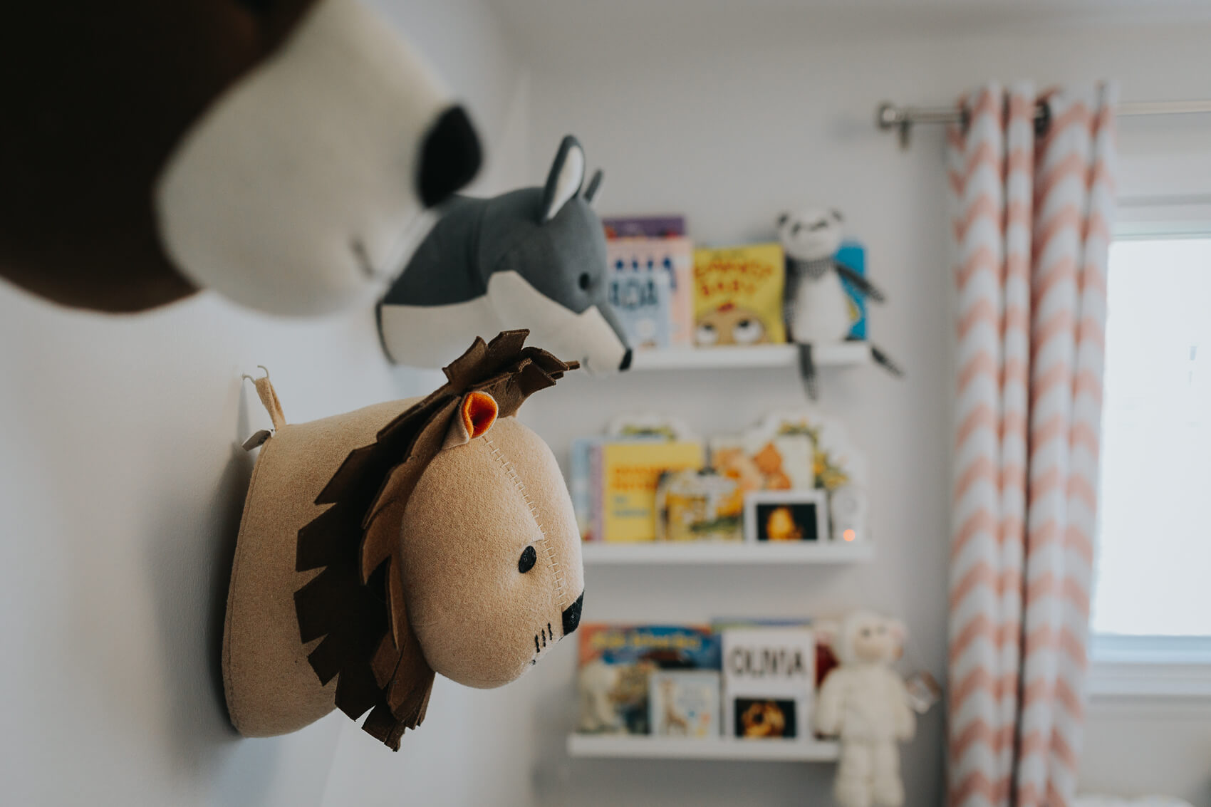 Picture of baby's nursery with animal stuffed toys on the wall.