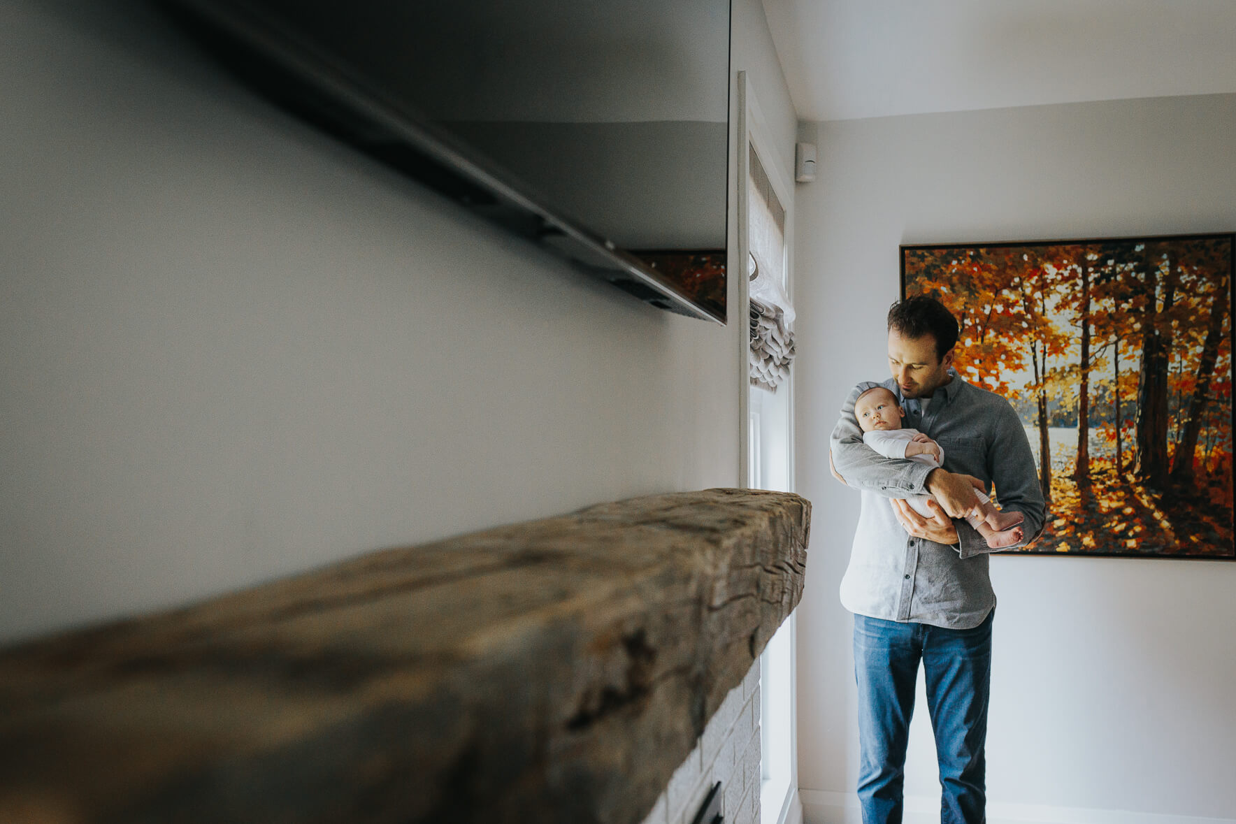 Artistic newborn photo showing dad holding his baby by the window.