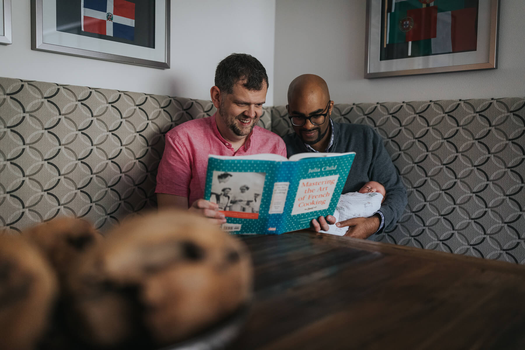 Same sex parents reading Julia Child's cookbook to their adopted daughter