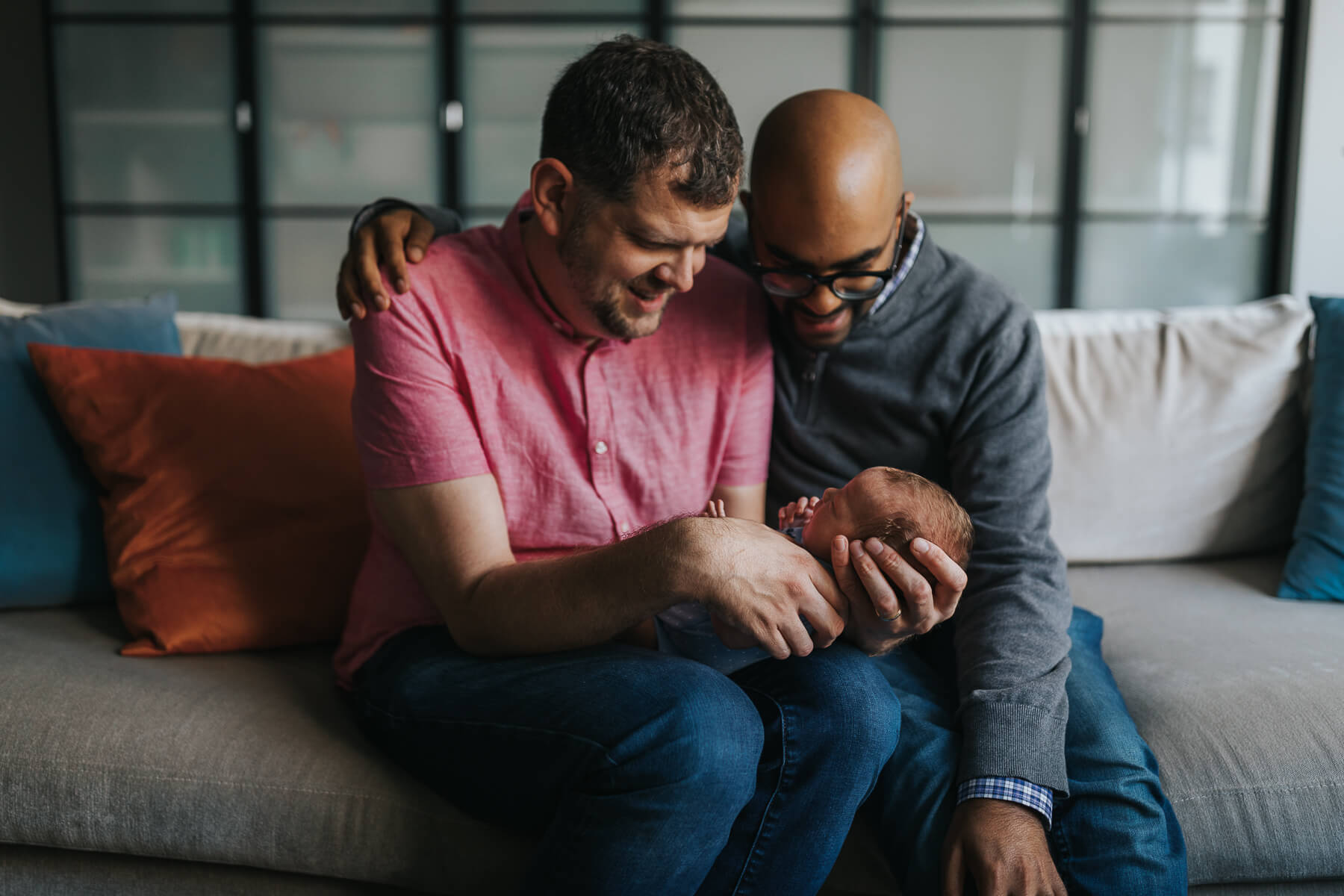 Gay couple sitting on couch in Kitchener with their baby daughter.