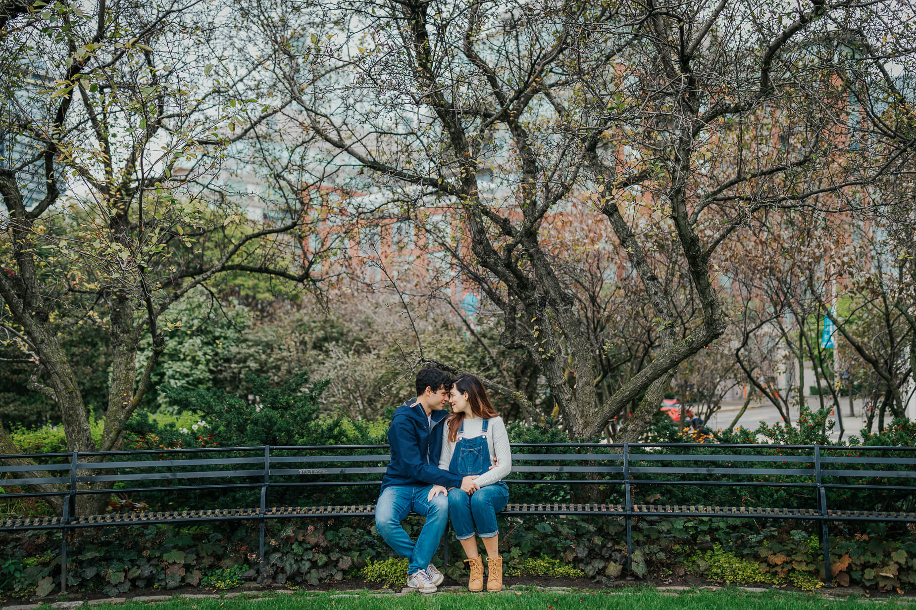 Pregnant couple sit on benches during a maternity photo shoot in Toronto Music Garden